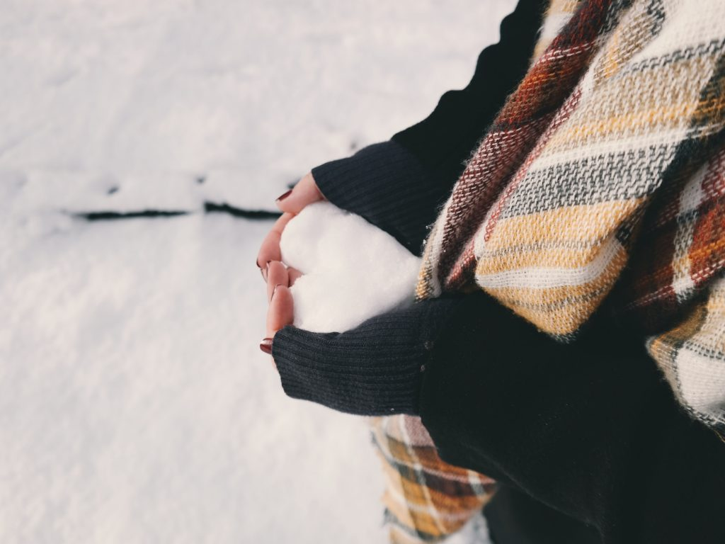 hands holding snow in winter